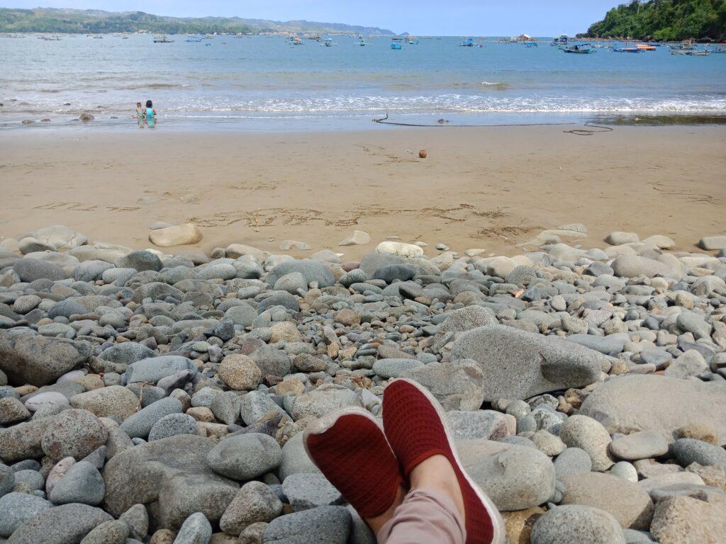 pengunjung beristirahat di atas hamparan batu Pantai Klatak
