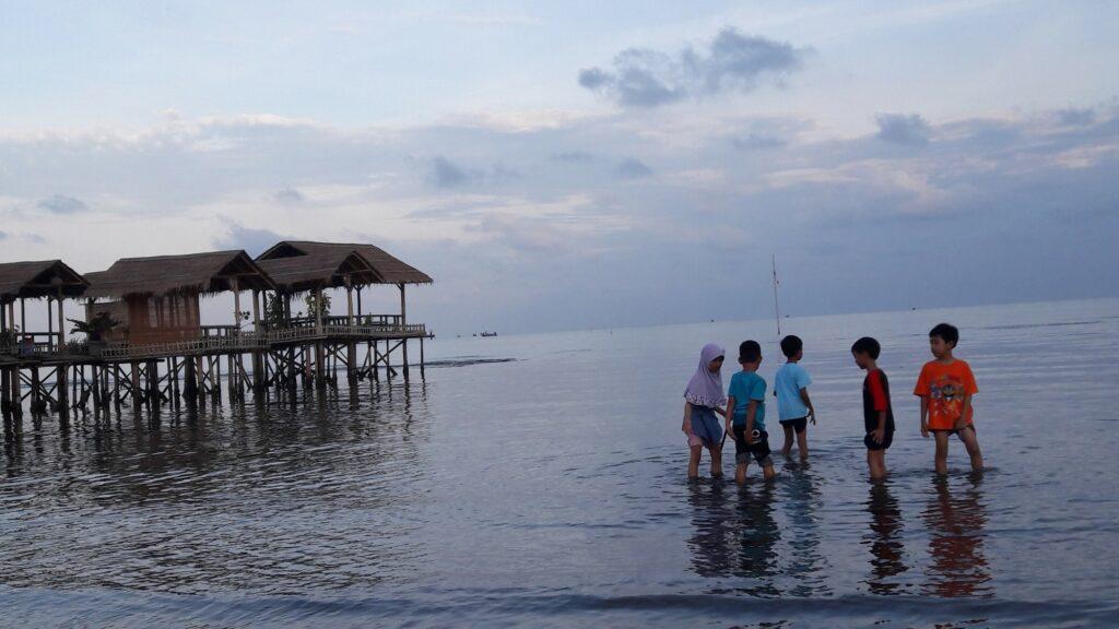 Anak - anak tengah Asyik Bermain di Tepi Pantai