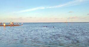 wisatawan sedang bermain dan berenang di tepi pantai kenyamukan