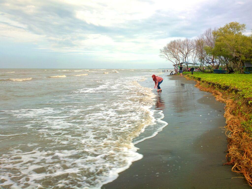wisatawan sedang bermain di tepi pantai muara gembong