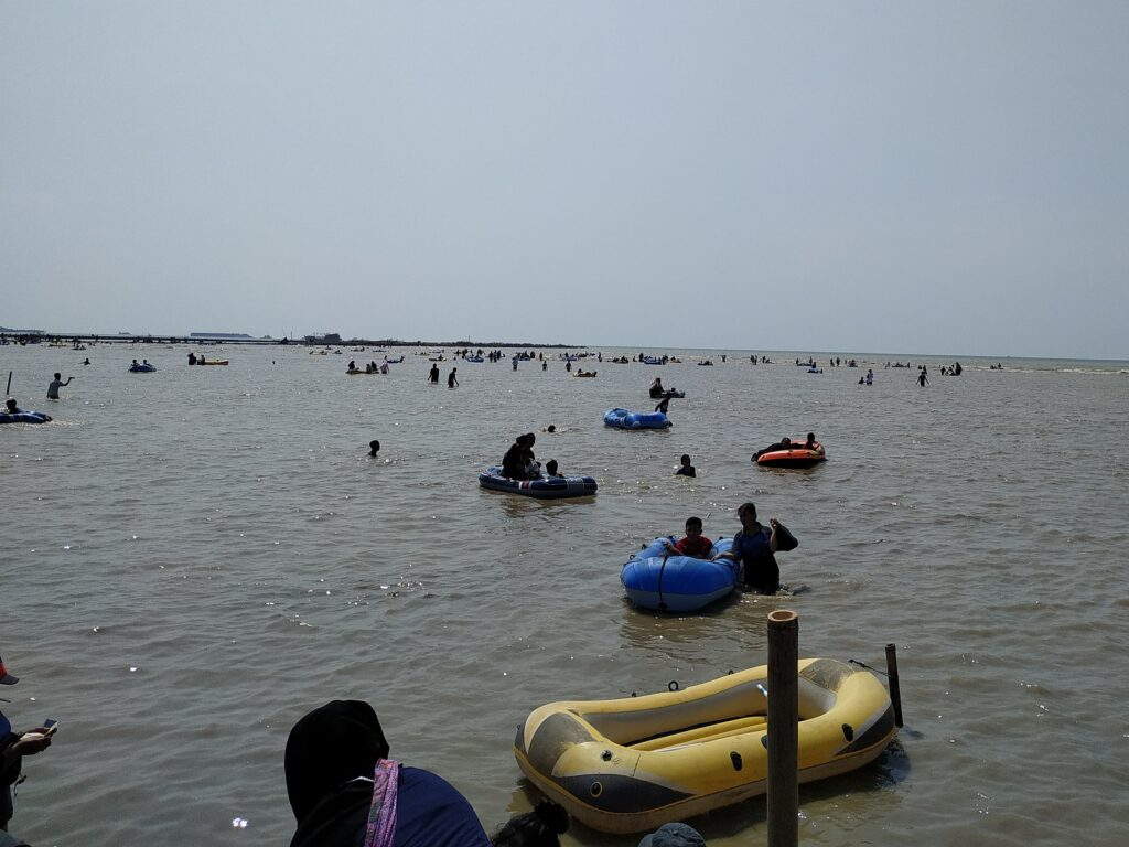 Wisatawan Bermain dengan Ceria di Pantai