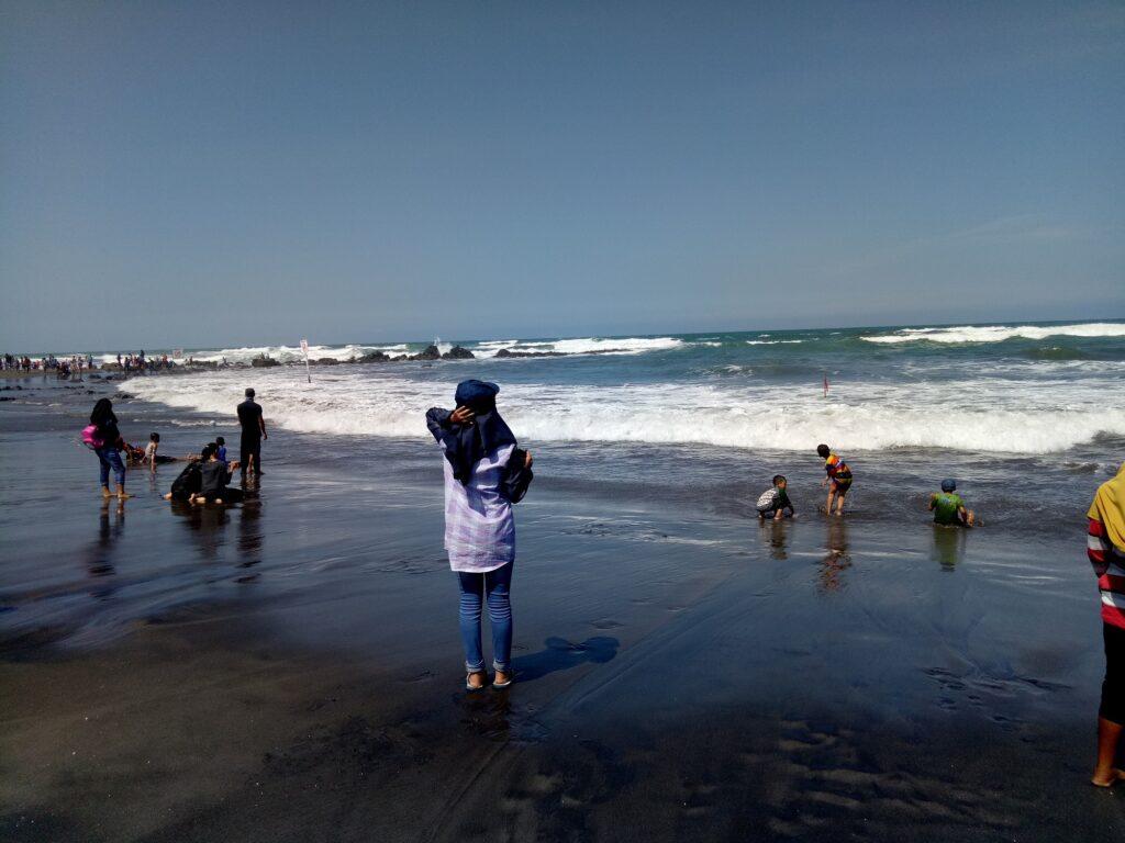 Wisatawan Tampak Asyik Bermain di Tepian Pantai