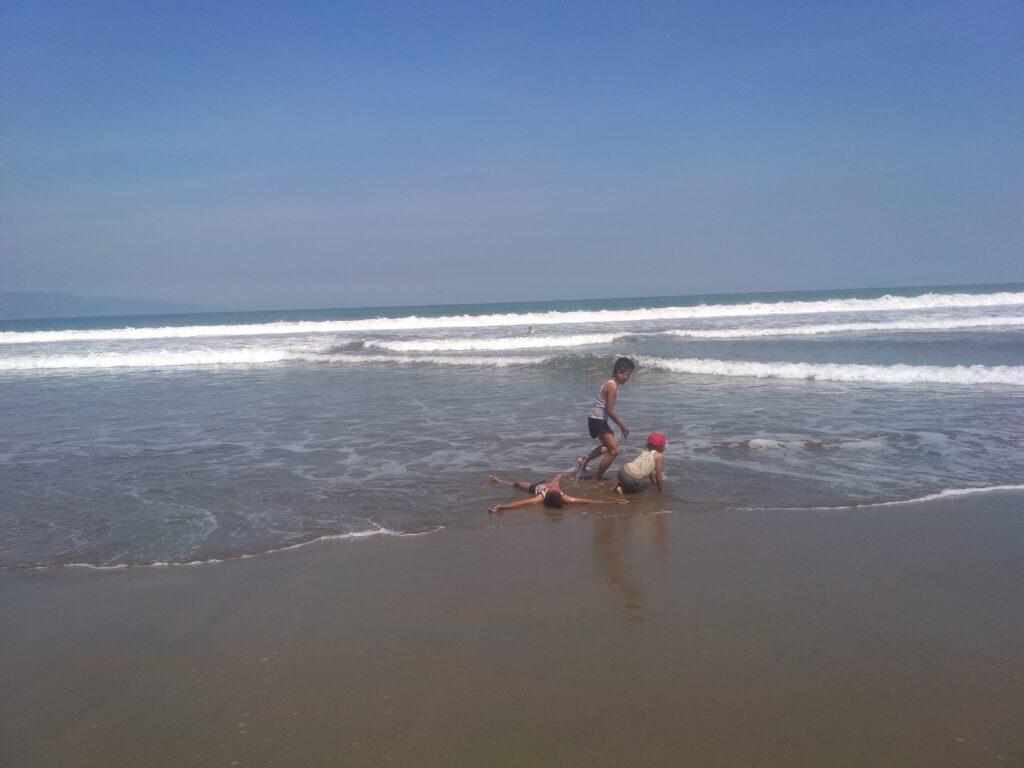 Anak - anak tengah asyik bermain di tepian pantai