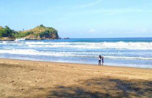 Area pantai berpasir putih halus serta ombak yang tenang di tepi pantai