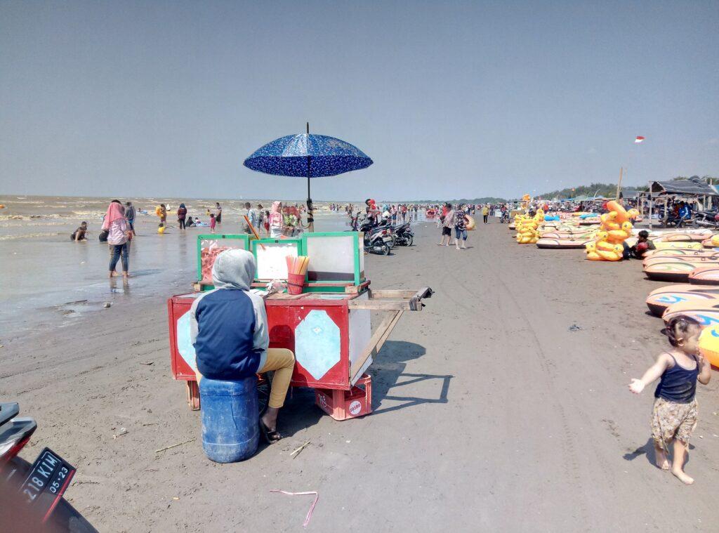 Ramai Wisatawan Memenuhi Tepi Pantai