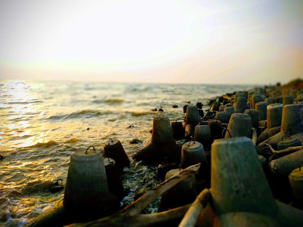 batu-batu pemecah ombak di bibir pantai