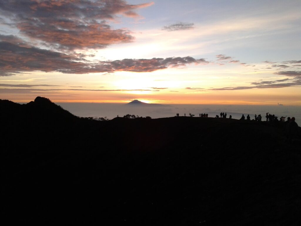 Matahari mengintop dari balik lapisan awan di timur