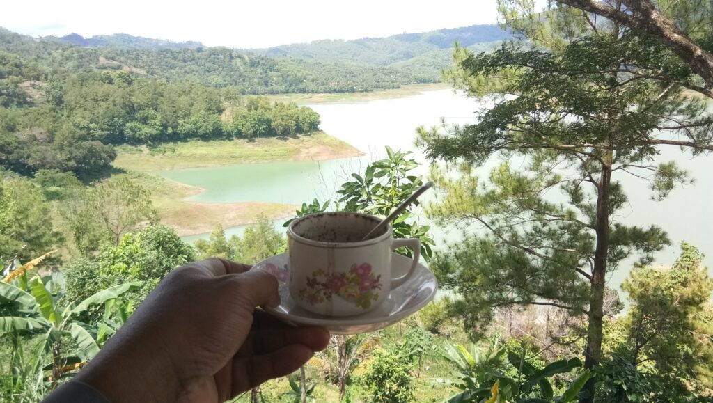 Secangkir kopi dengan latar panorama danau