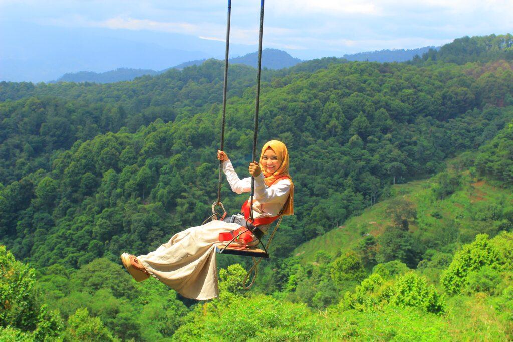 Pengunjung berfoto dari ayunan di Panorama Pabangbon tempat wisata di Bogor bertemakan taman selfi