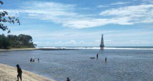 Area tepi Pantai Sindangkerta berlatar mercusuar