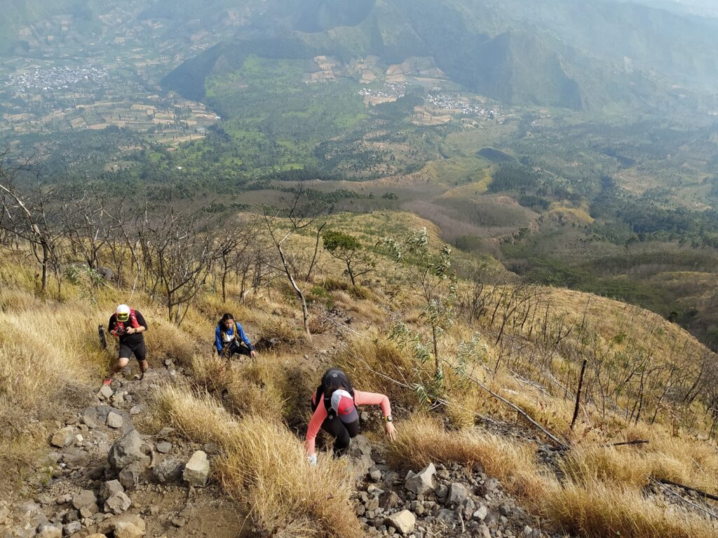 sejumlah pendaki berusaha melewati jalur menanjak yang dipenuhi bebatuan