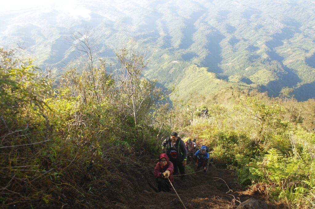 Pendaki memegang tali sambil menaiki tanjakan ke puncak