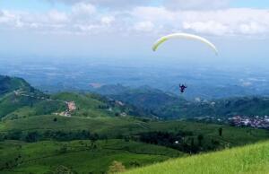 terbang paralayang di atas perbukitan hijau