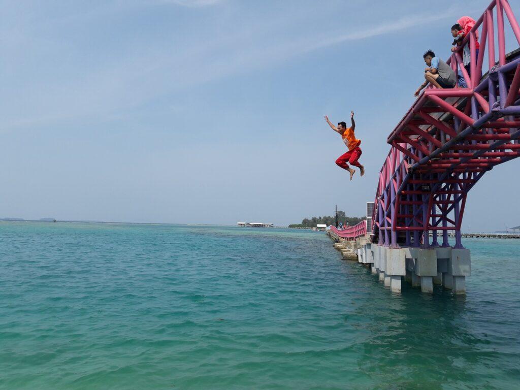 Wisatawan melompat ke laut dari jembatan yang menghubungkan pulau tidung besar dan kecil