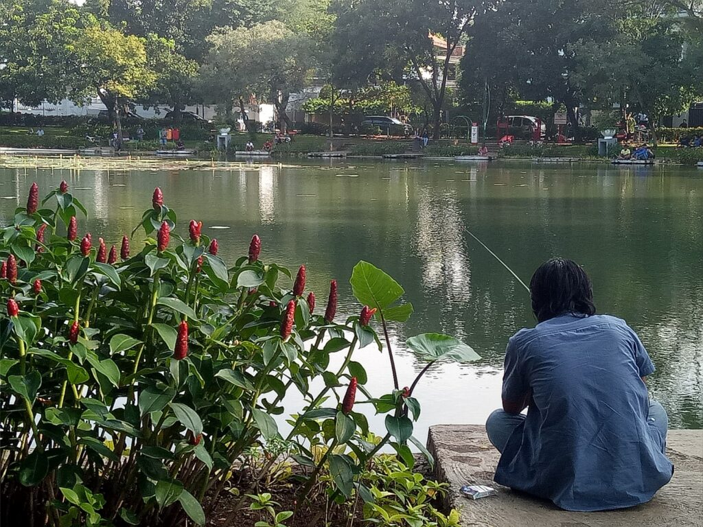 Duduk di tepi danau untuk memancing