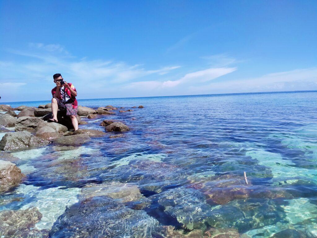 Wisatawan bersantai di batu karang