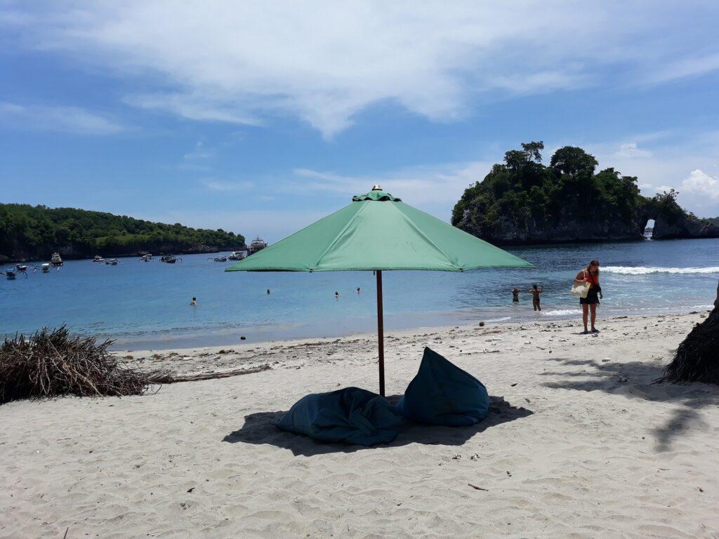 Payung Menaungi Bean Bag untuk Bersantai di Tepi Pantai