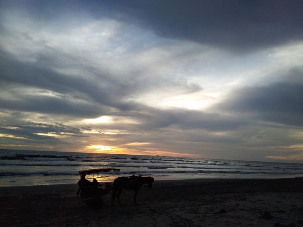 Delman berhenti di area pantai tepat ketika matahari tenggelam