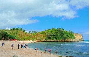 wisatawan bermain di tepi pantai ngudel