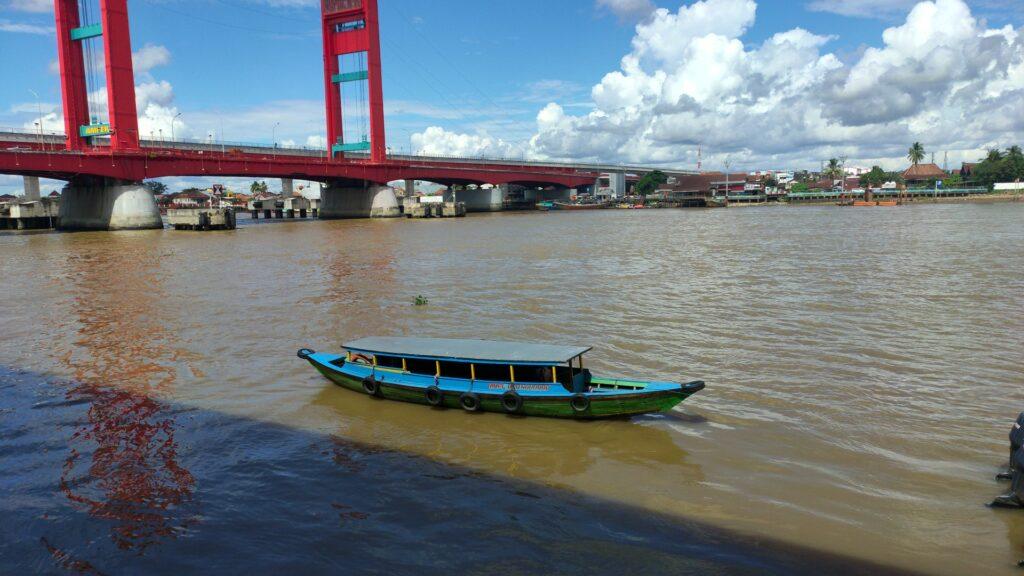 Sebuah kapal melintas dekat jembatan