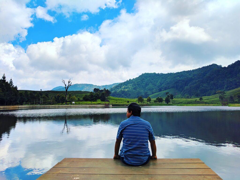Pengunjung duduk menikmati suasana danau telaga saat