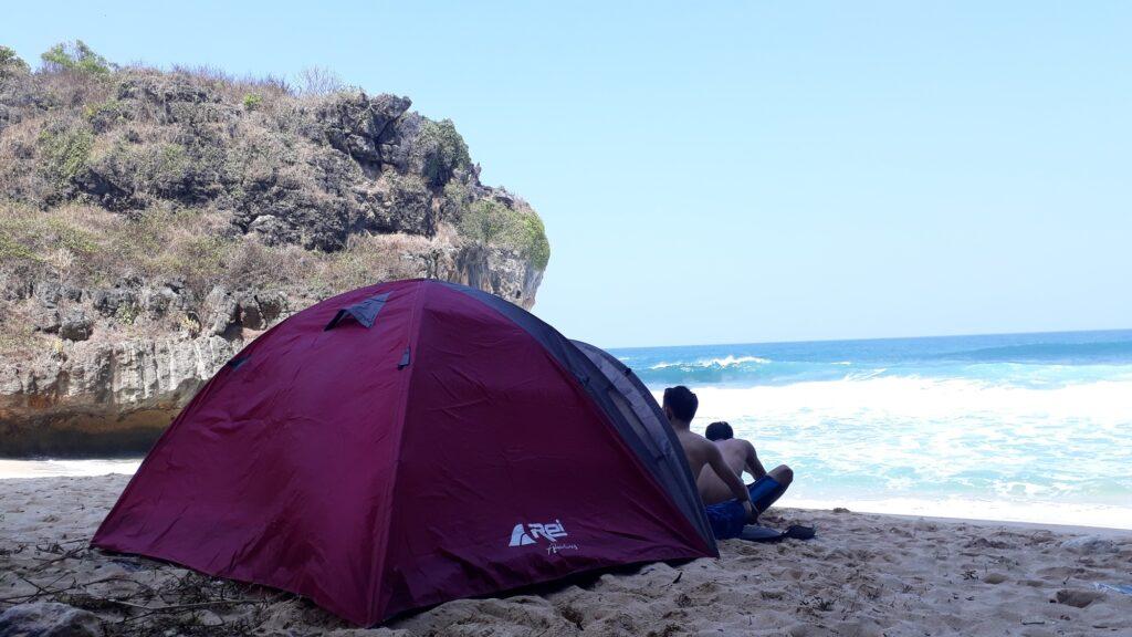 Pengunjung bersantai di depan tenda tepi pantai