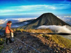 Pengunjung bersandar di pagar pengaman kawah memandangi Puncak Pangrango