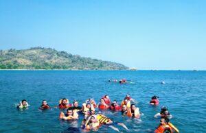 wisatawan sedang berenang dan snorkeling di pantai palangpang