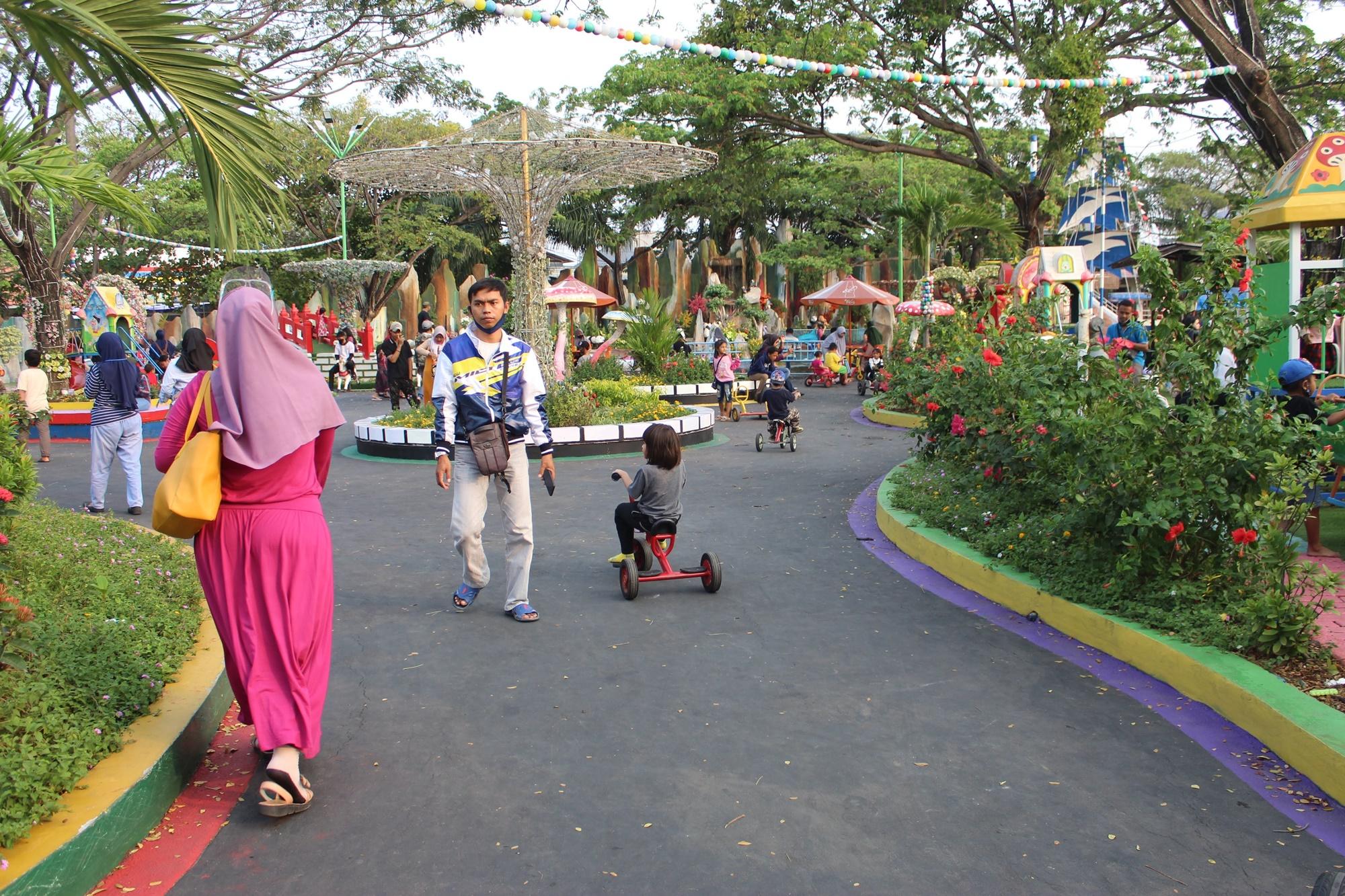 Pengunjung berkeliling taman dengan sepeda