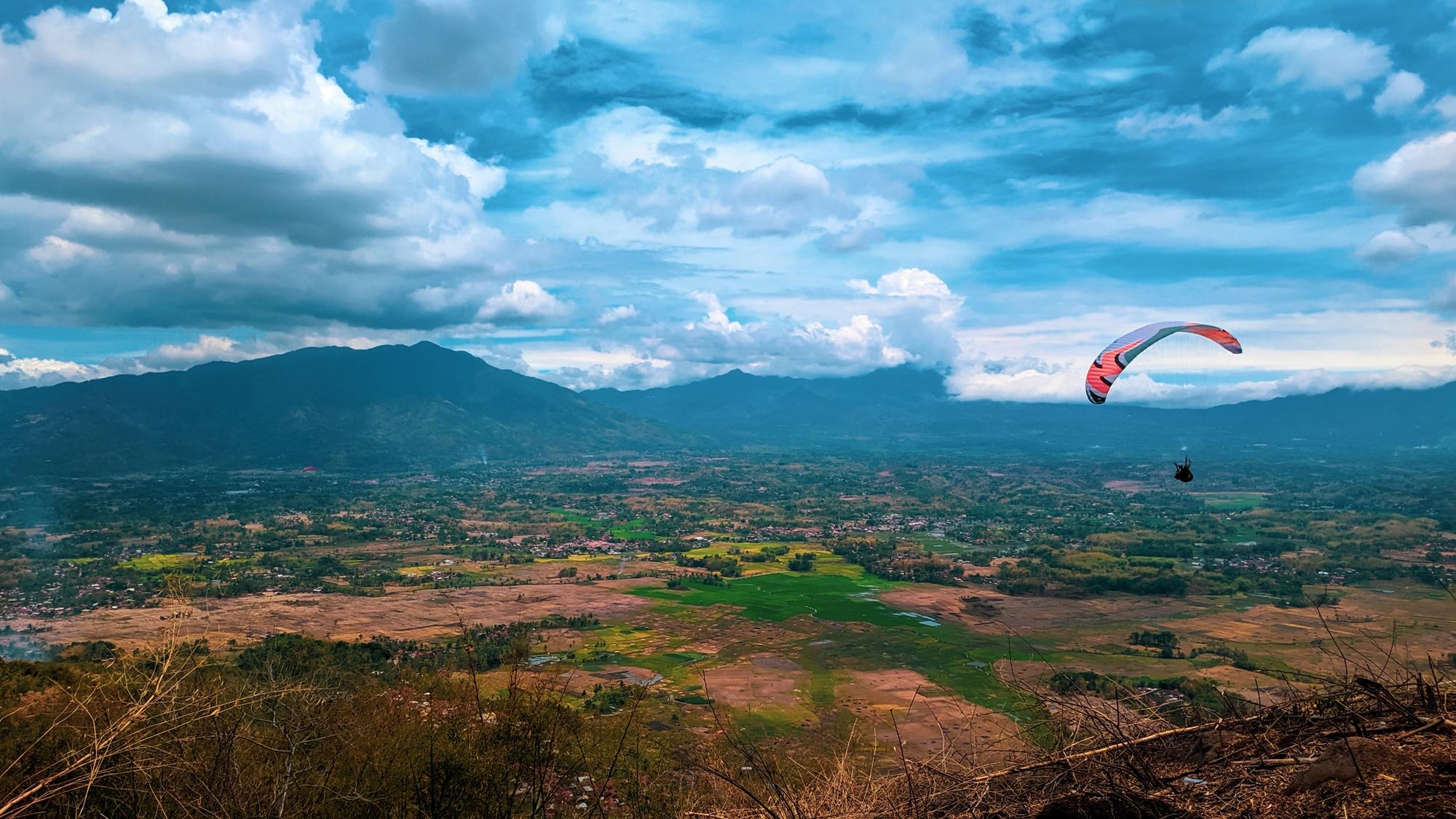 Atlet paralayang meluncur di udara